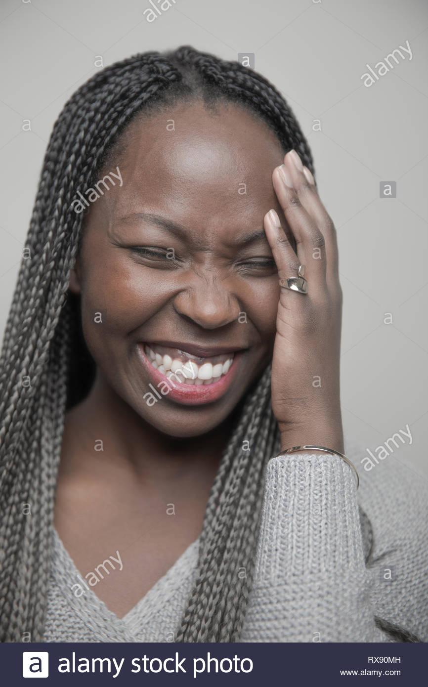 Porträt unbeschwert Schöne junge afrikanische amerikanische Frau mit langen schwarzen Zöpfen lachen Stockbild