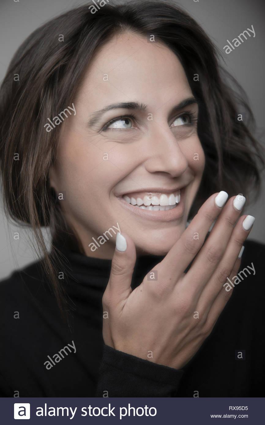 Portrait schöne junge brünette Frau lachend und Suchen Stockbild