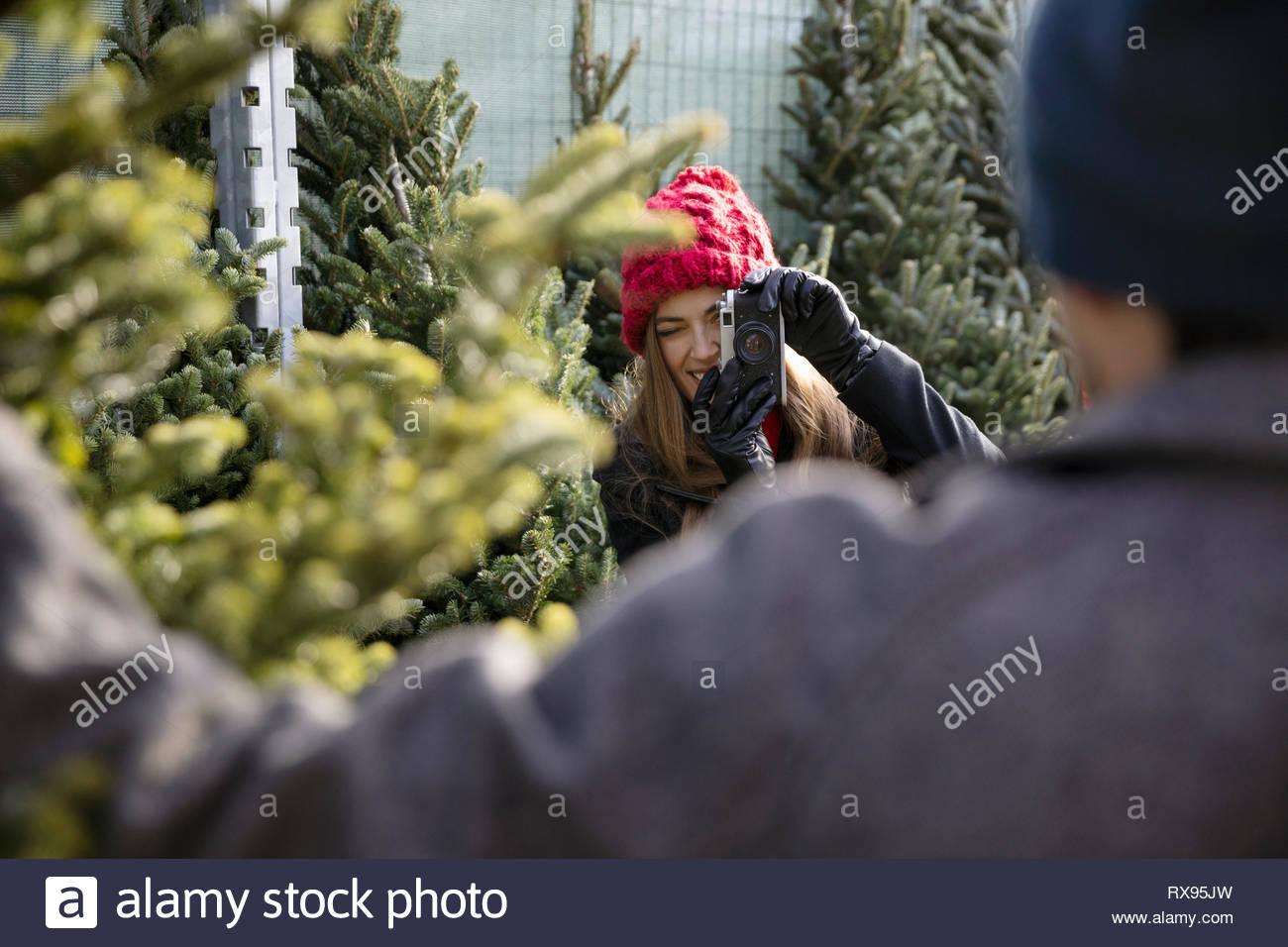 Frau mit Kamera fotografieren Freund mit Weihnachtsbaum am Weihnachtsmarkt Stockbild