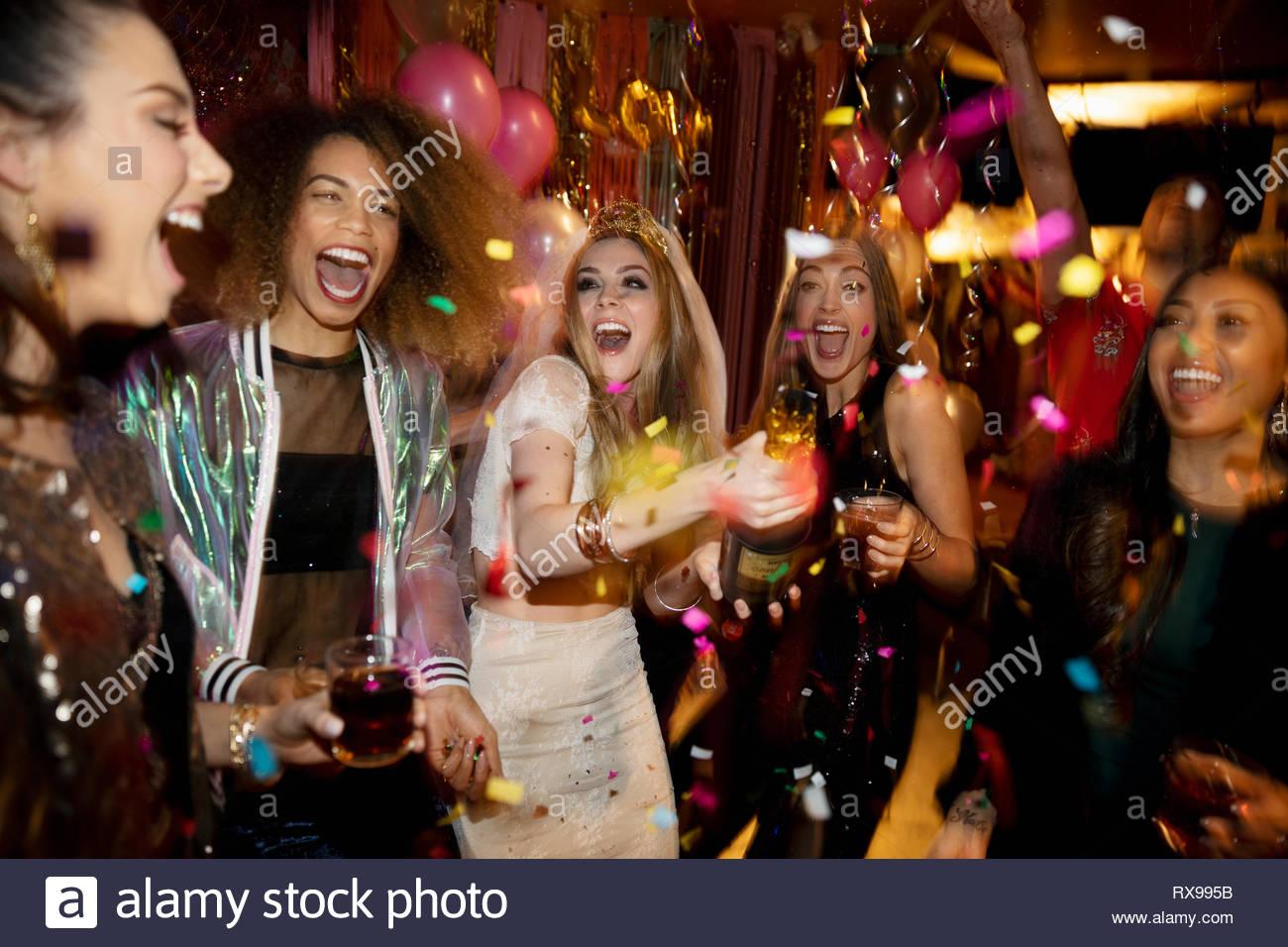 Konfetti über gelacht Bachelorette und Freunde in Nachtclub Stockbild