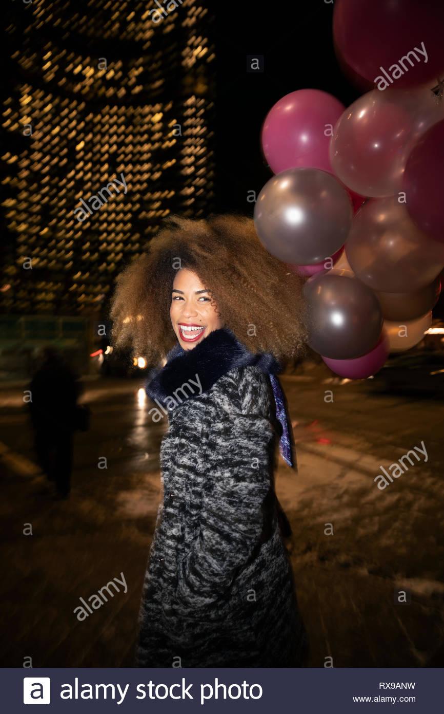 Portrait ausgelassene junge Frau mit Ballons auf Urban Street bei Nacht Stockbild
