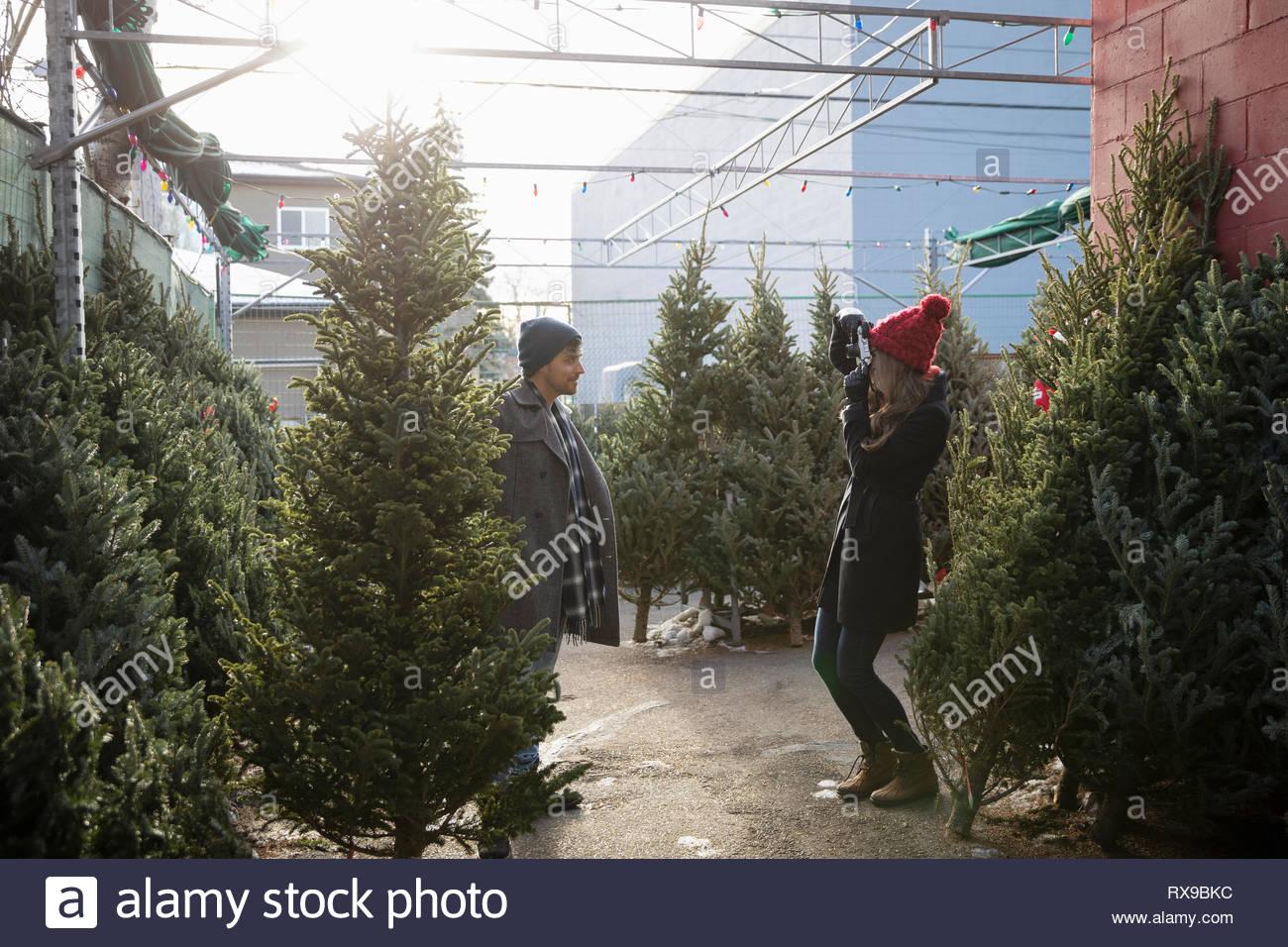 Paar mit Kamera Handy Shopping für Weihnachtsbaum am Weihnachtsmarkt Stockfoto