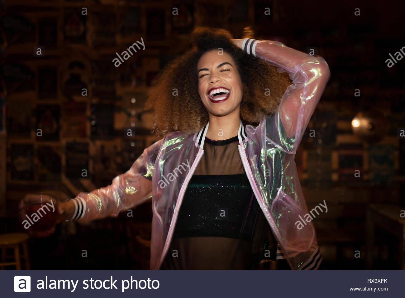 Lachen, quirlige junge Frau trinkt Cocktail in Nachtclub Stockbild