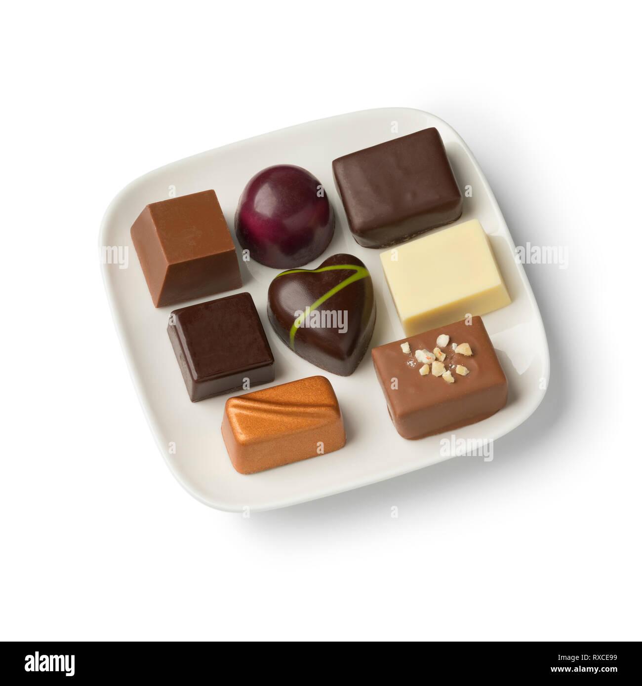 Teller mit sortierten Schokolade Bonbons auf weißem Hintergrund Stockbild