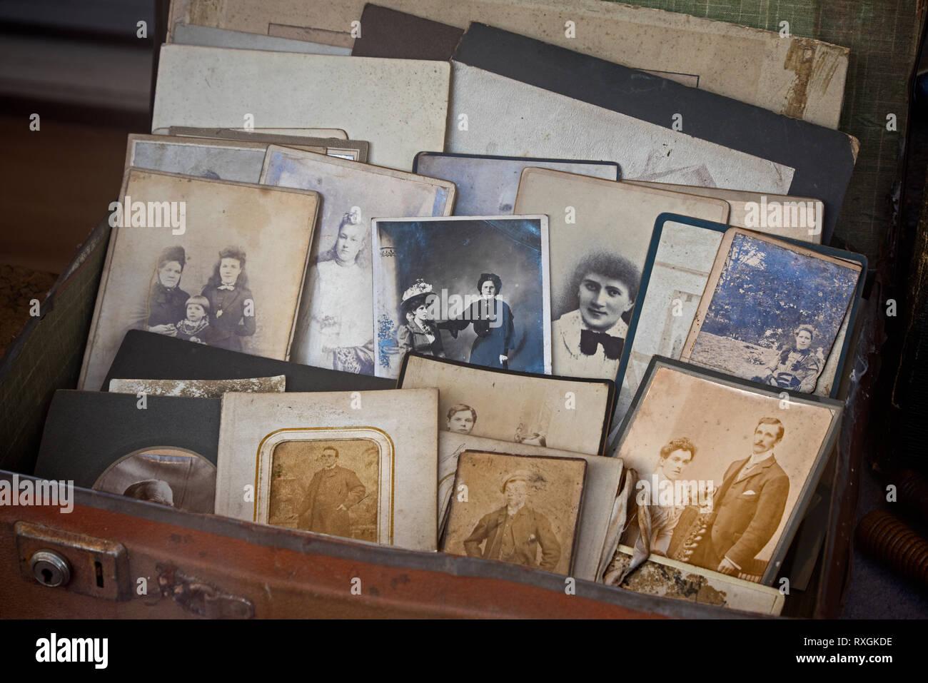 Ein Koffer voller alten Vintage Fotos im Fenster eines Charity Shop in Edinburgh, Schottland, Großbritannien. Stockbild