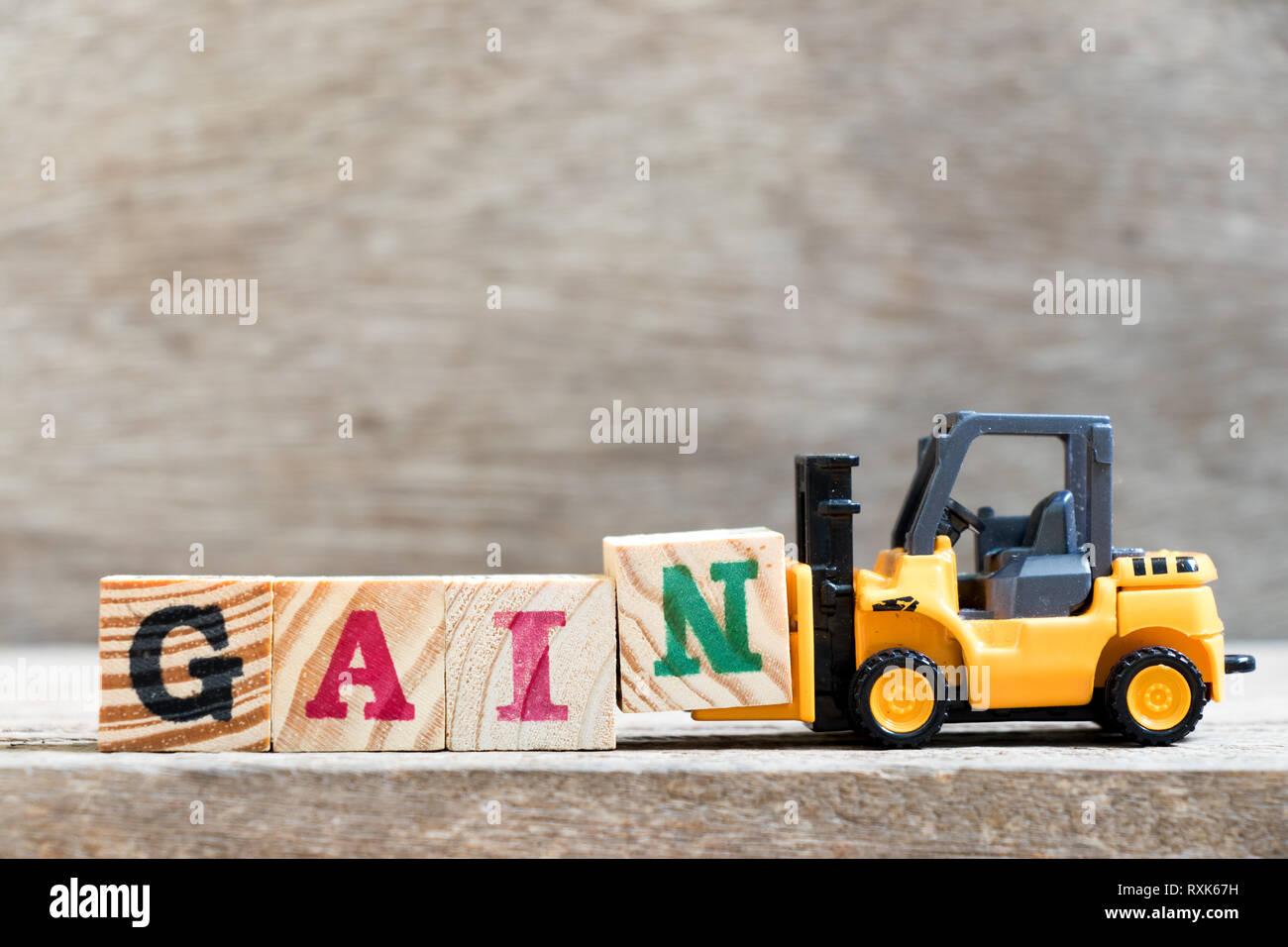Spielzeug Gabelstapler halten schreiben Block N in Wort Gewinn aus Holz Hintergrund Stockbild