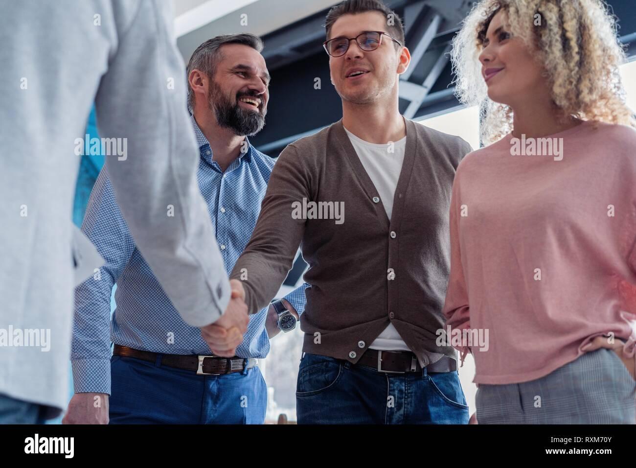Froh, mit Ihnen zu arbeiten! Junge moderne Männer in Smart Casual Wear Hände schütteln und lächelnd, während in der kreativen Arbeiten im Büro. Stockfoto