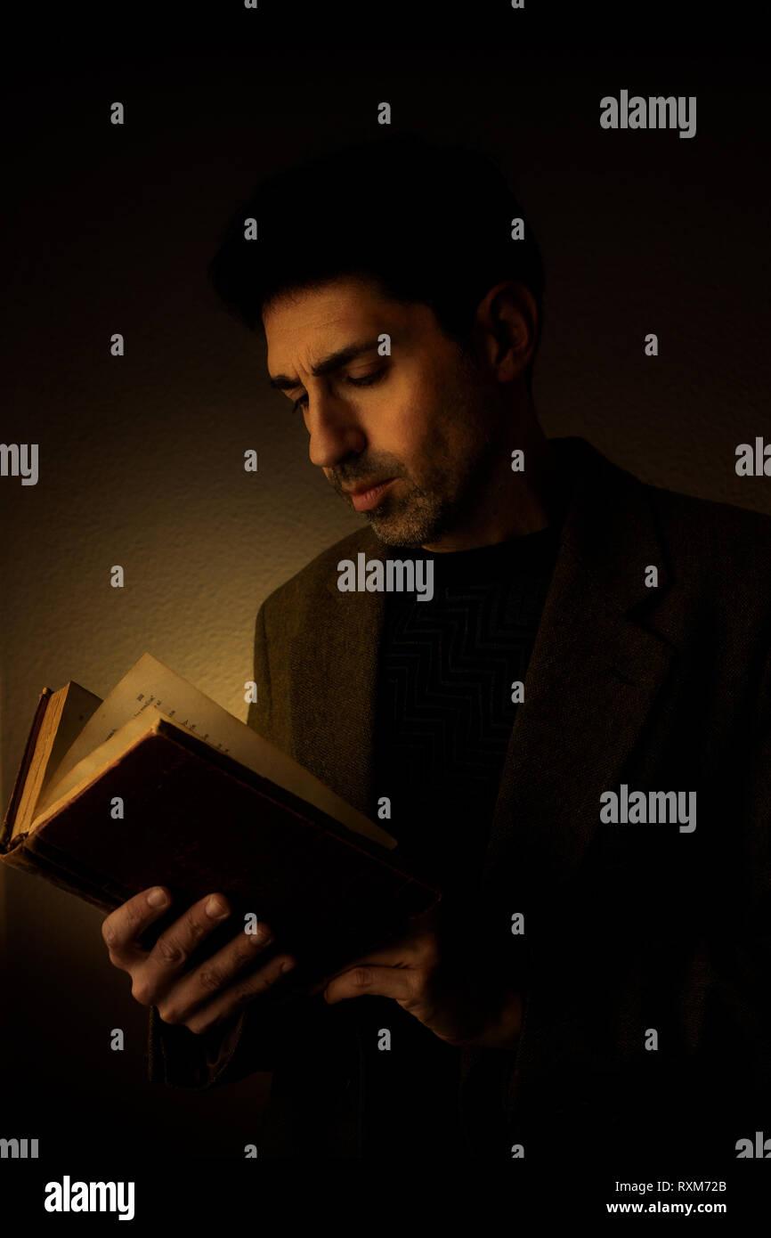 Mann lesen ein altes Buch in einer dunklen Umgebung. Stockbild