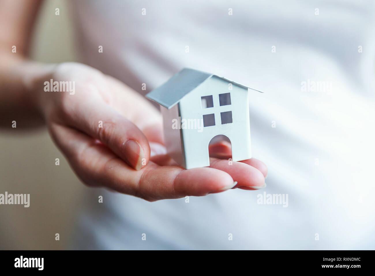 Weiblich frau Hände halten kleine Miniatur weiß Spielzeug Haus. Hypothek Sachversicherung traum Umzug und Immobilien Konzept Stockfoto