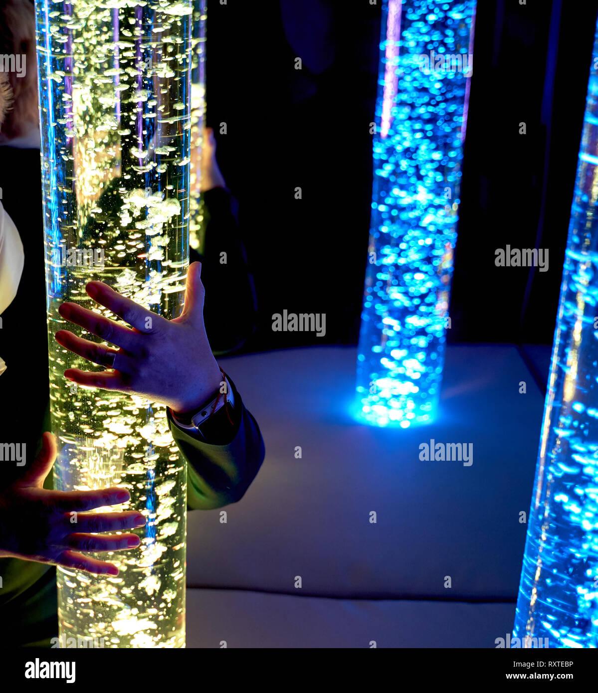 Therapie sensorische Stimulierung multi sensorische Zimmer, Frau Interaktion mit farbigen Lichtern bubble Röhrenlampe während der Therapie healthcare Seniorenheim sessi Stockbild