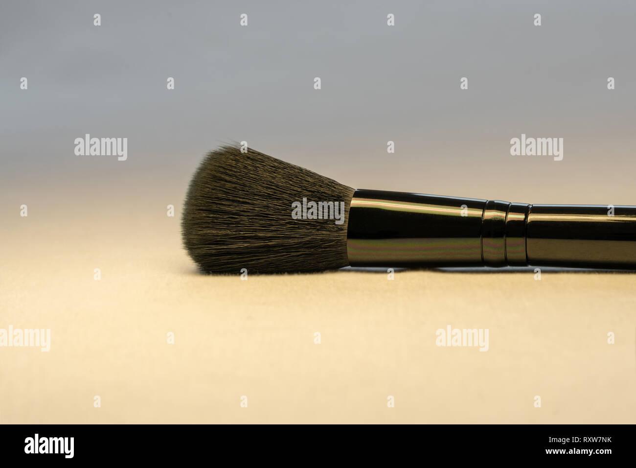 Ein schwarzes Make-up Teint Pinsel auf hellen Hintergrund, schließen Sie das Bild. Schönheit und Hautpflege Konzept. Stockbild