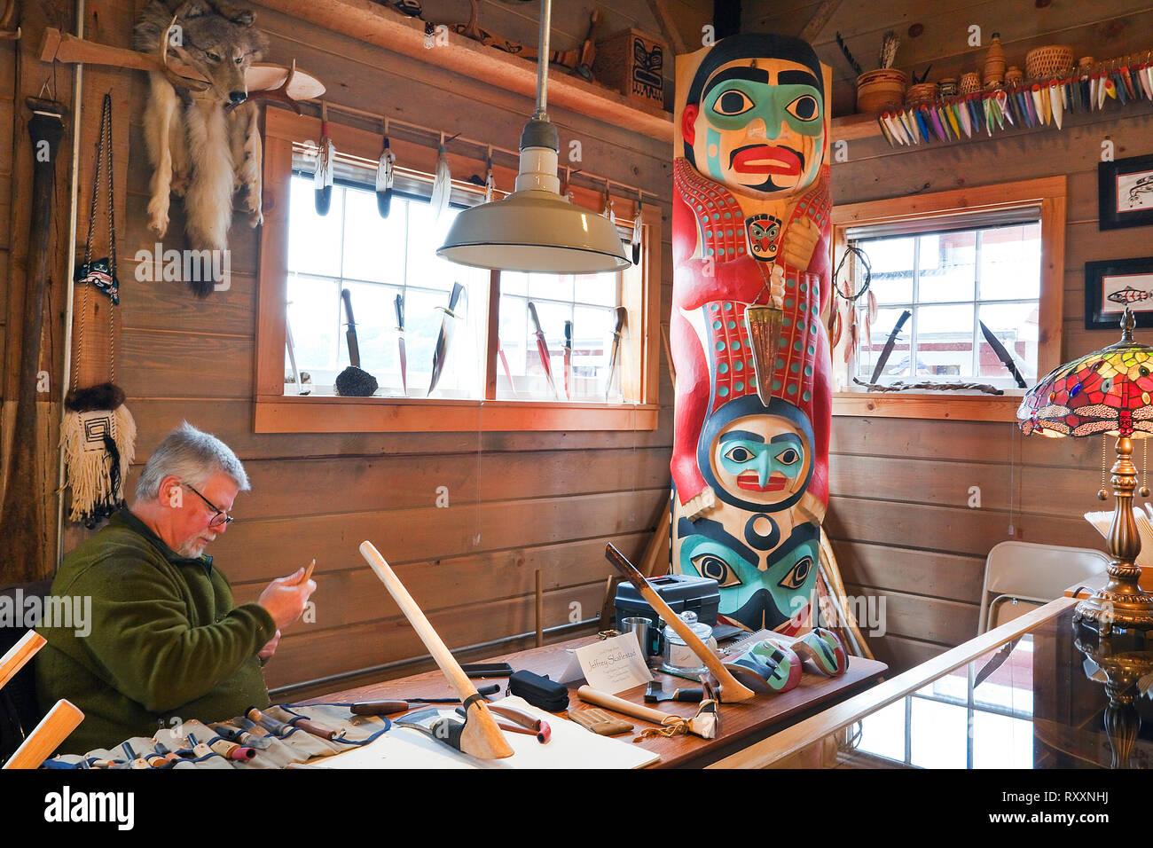 """Norwegian-Tinglit carver Jeff Skaflestad an einem Arbeit Tabelle innerhalb der Icy Strait Point Cannery Museum. Das Totem in der Ecke ist mit dem Titel """"Hawkt' Zahn Stockbild"""
