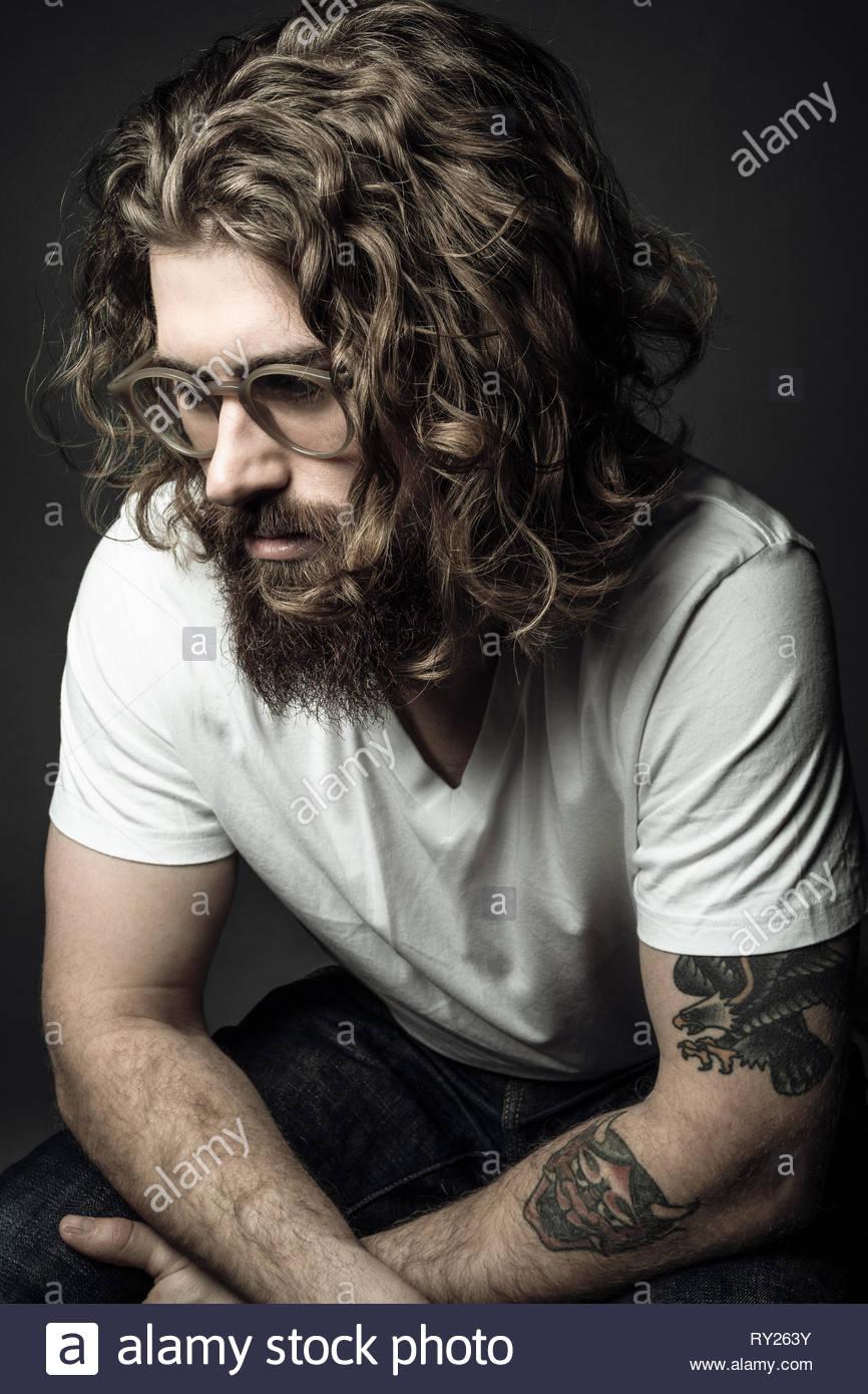 Nachdenklich hübscher junger Mann mit lockigem Haar und Tattoos Stockbild