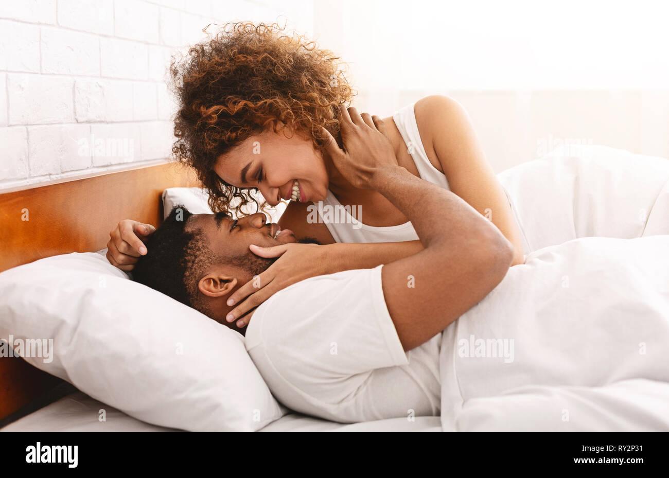 African-American Girl kissing Ihren liebsten im Bett Stockfoto