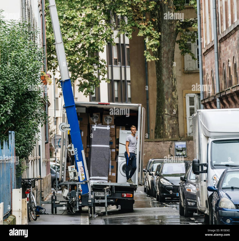 Straßburg, Frankreich - 12.September 2017: Square Image der jungen männlichen Arbeitnehmer in das Fahrzeug warten auf den hydraulischen Aufzug Boom ein weiteres Paket während Home Umzug zu liefern Stockbild