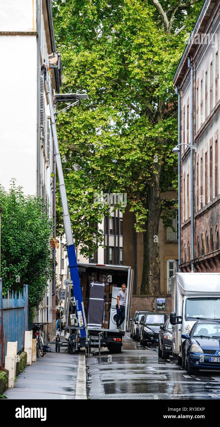 Straßburg, Frankreich - 12.September 2017: Junge männliche Arbeiter warten auf den hydraulischen Aufzug Boom ein weiteres Paket während Home Umzug zu liefern Stockbild