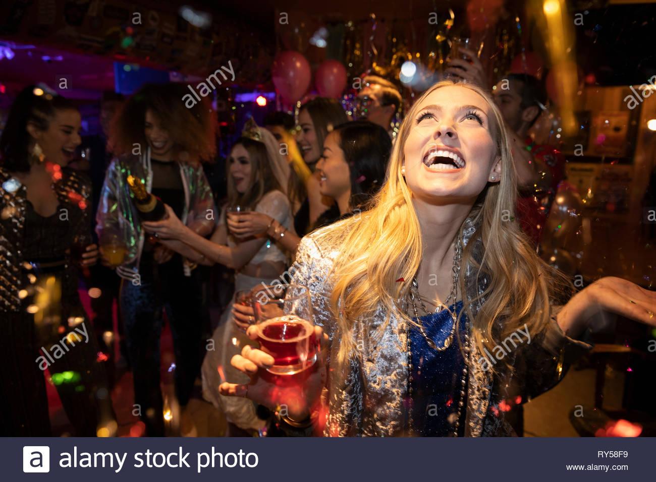 Konfetti über unbeschwerte junge Frau trinkt Cocktail in Nachtclub Stockbild