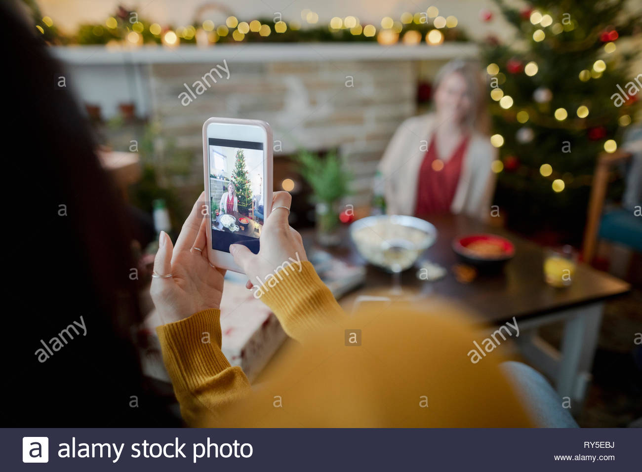 Frau mit Kamera Handy fotografieren Freund in Weihnachten Wohnzimmer Stockbild