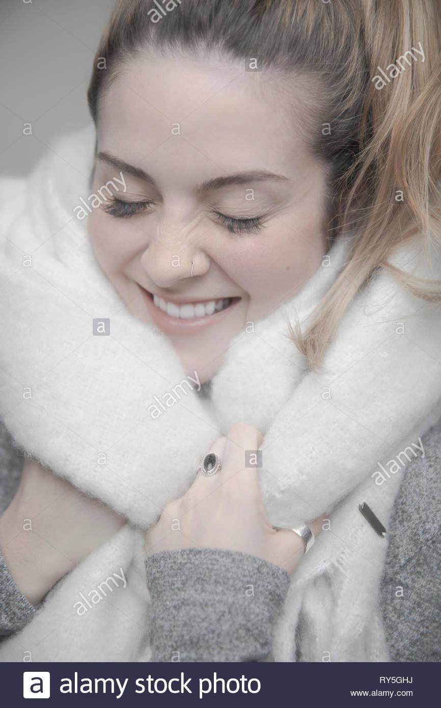 Portrait unbeschwerte junge blonde Frau in warme Decke eingewickelt Stockbild