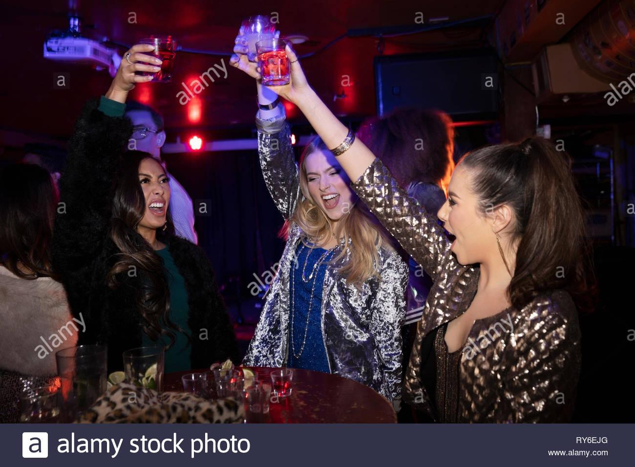 Ausgelassene junge Frauen Freunde toasten Cocktails in Nachtclub Stockbild