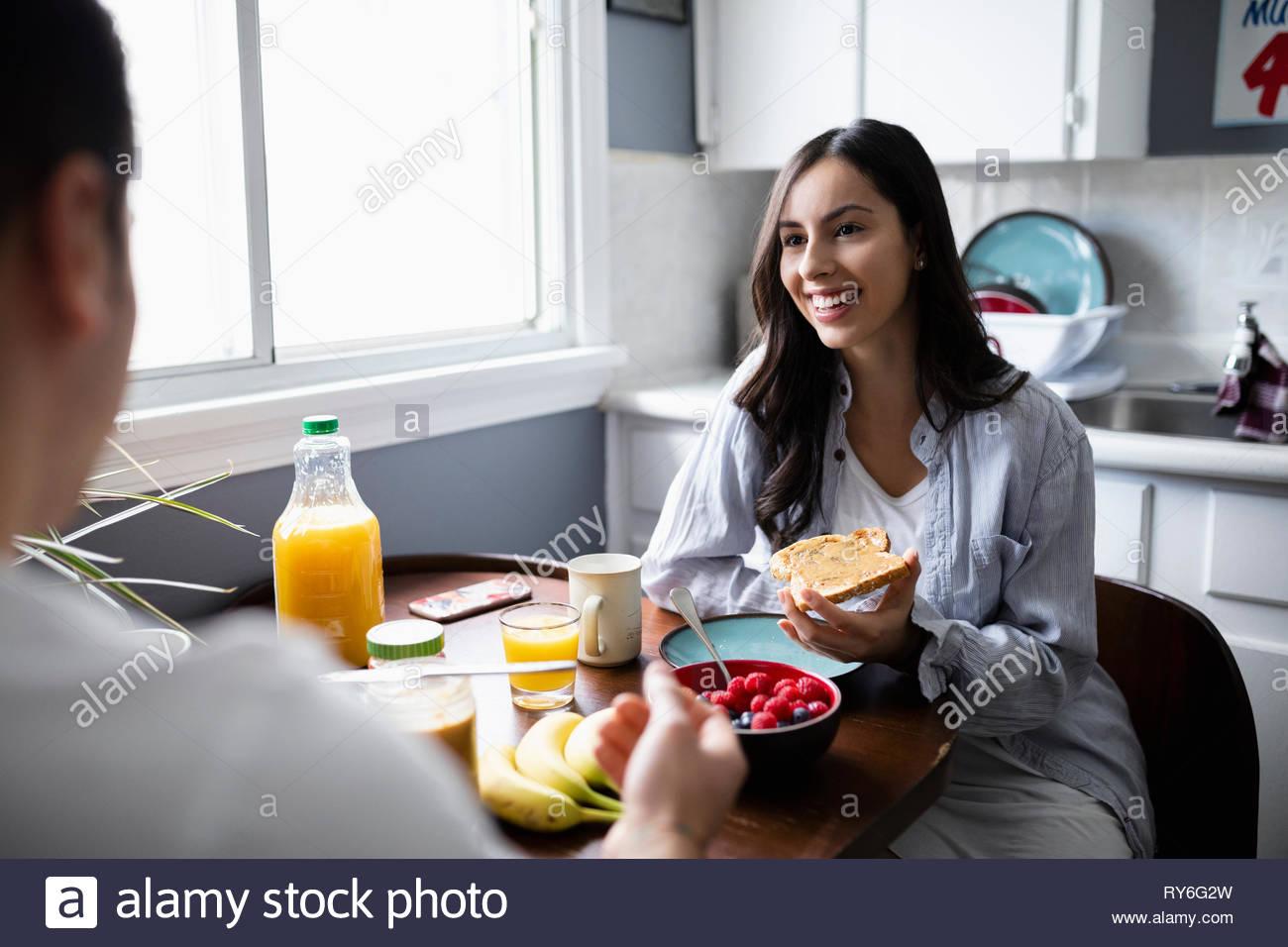 Glückliche junge Frau Latinx essen Frühstück mit Freund in der Küche Stockbild