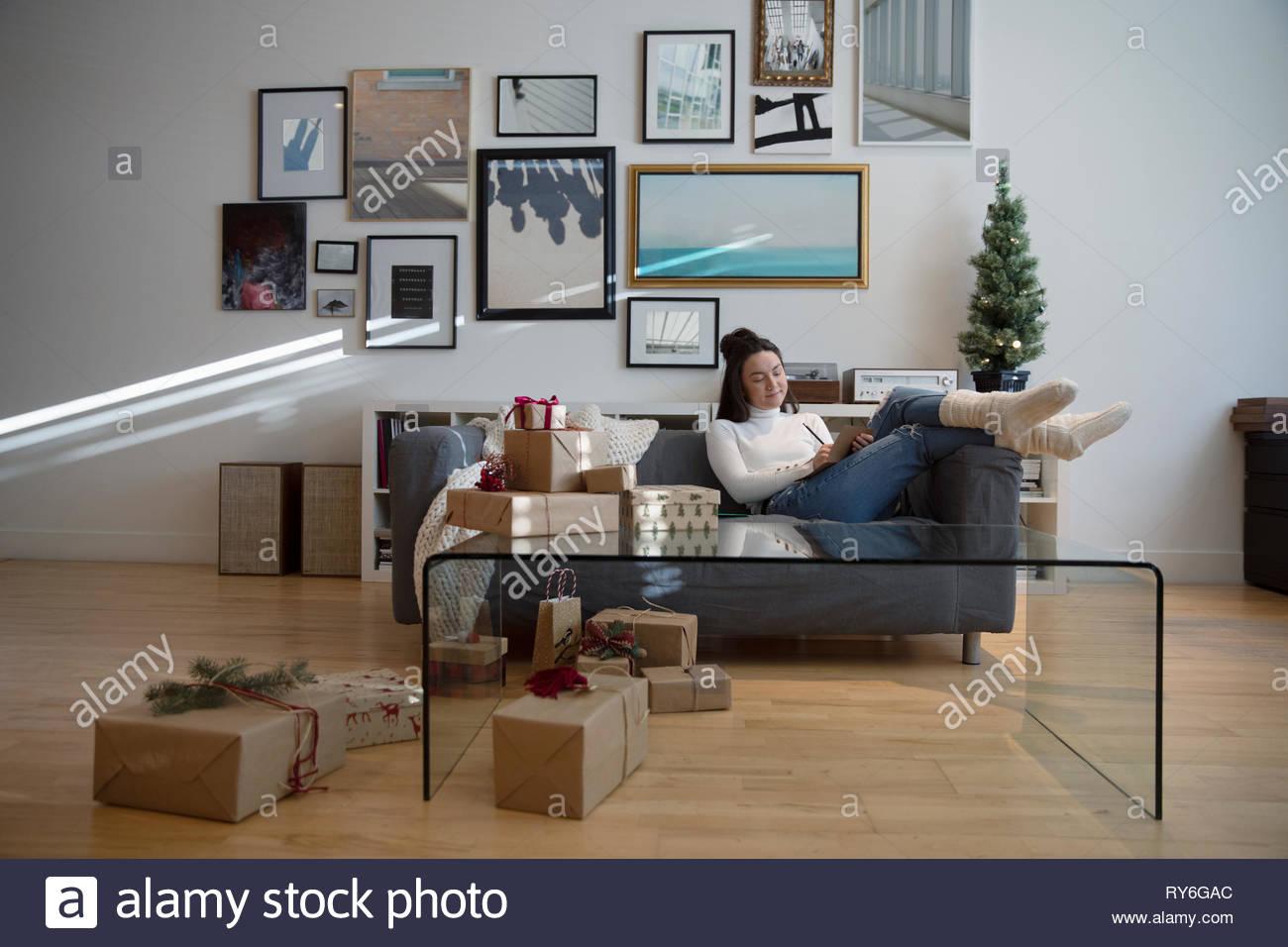 Gemütliche junge Frau Verpackung Weihnachtsgeschenke im Wohnzimmer Stockbild