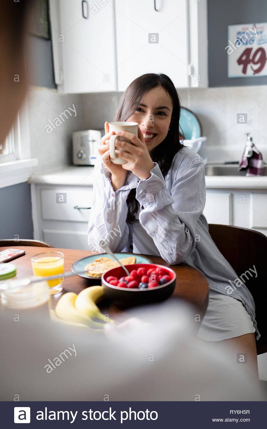 Glückliche junge Frau Latinx Frühstück mit Freund in der Küche Stockbild