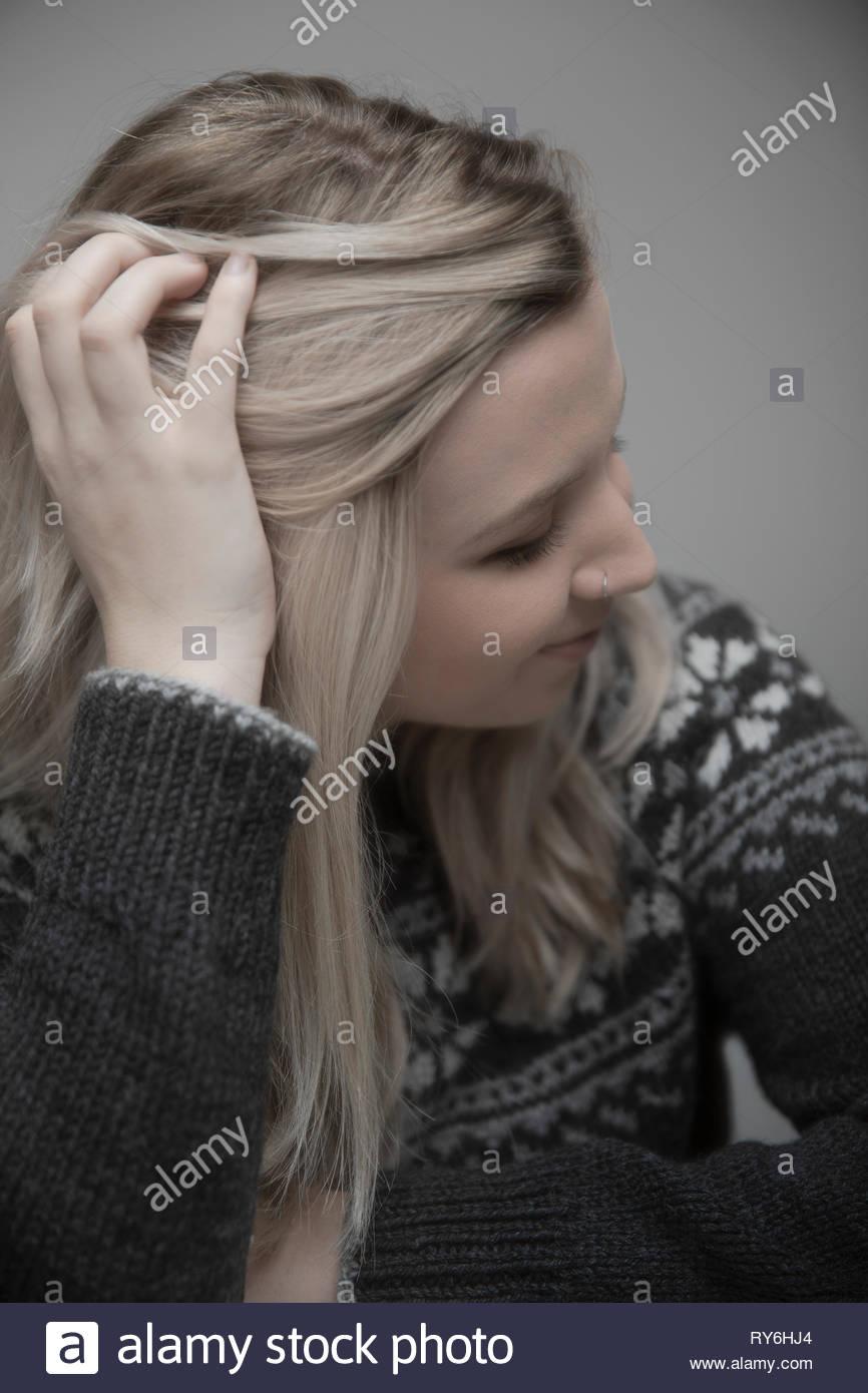 Portrait schöne junge blonde Frau mit Nasenring und Hand im Haar Stockbild