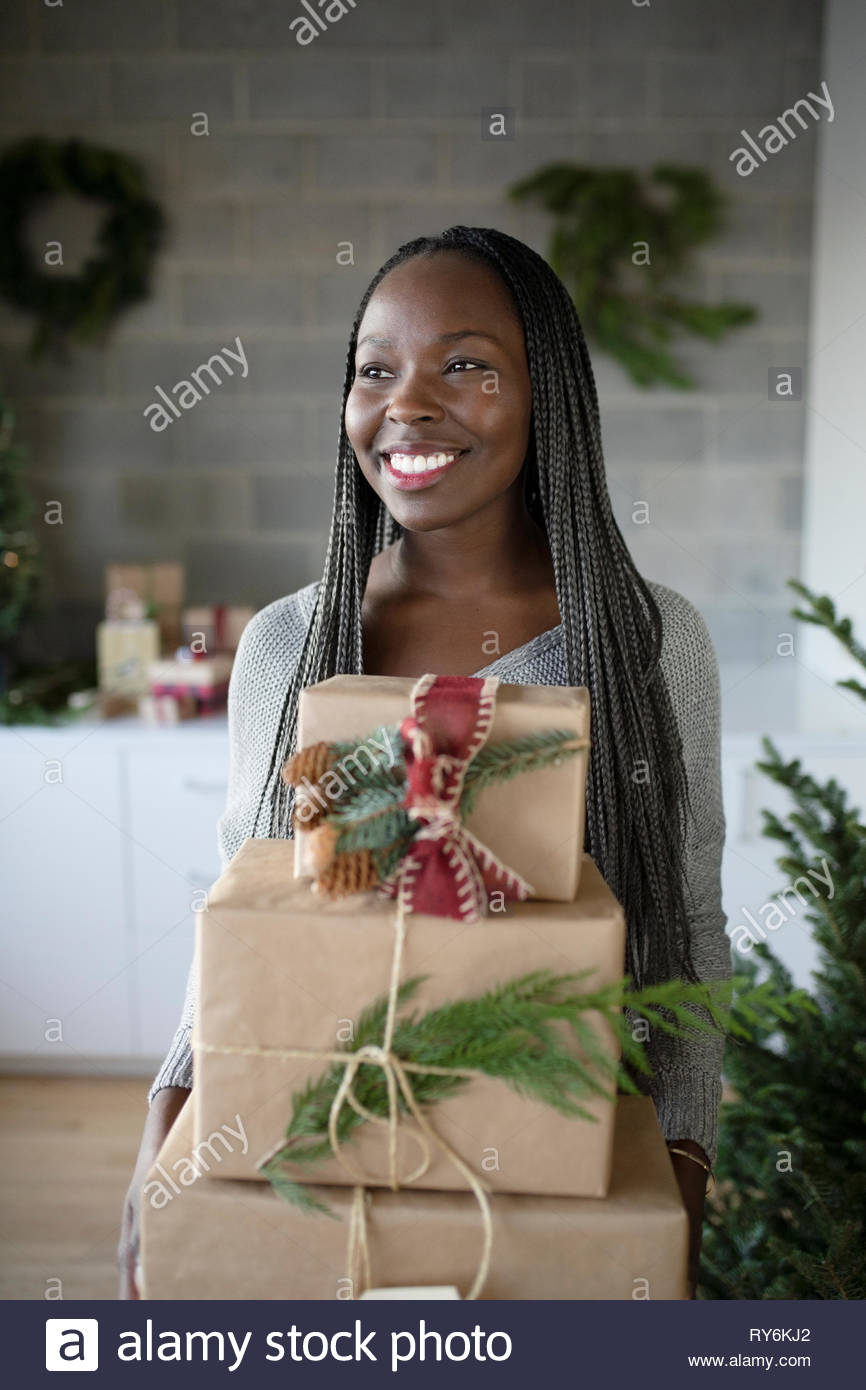 Glückliche junge afrikanische amerikanische Frau mit der Weihnachtsgeschenke Stapel Stockbild