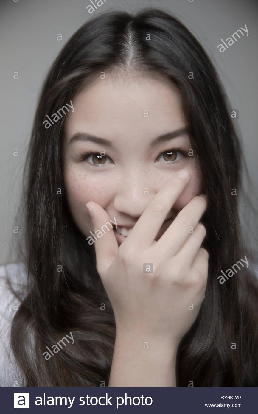Portrait schöne Brünette junges Mädchen mit braunen Augen lachend mit der Hand über den Mund Stockbild