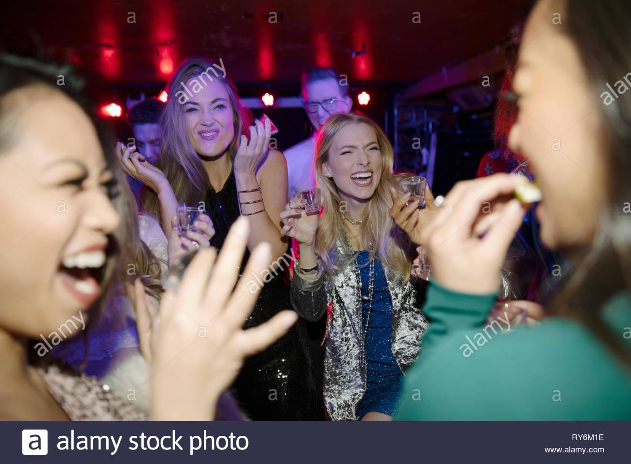 Junge Frauen, die Freunde, die tequila Schüsse im Nachtclub Stockbild