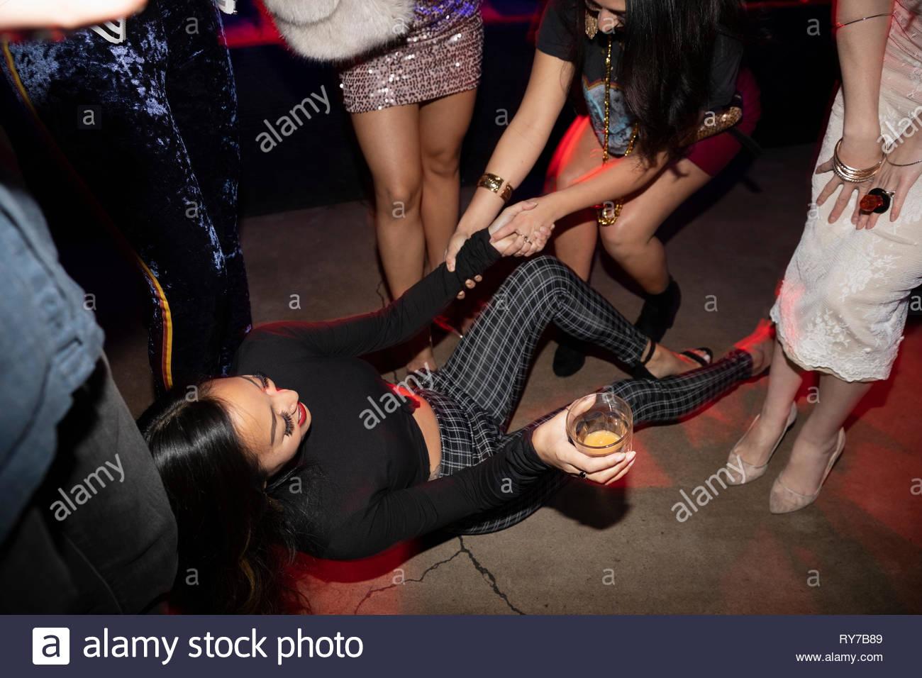 Freunde helfen Frau fallen auf Diskothek Etage Stockbild