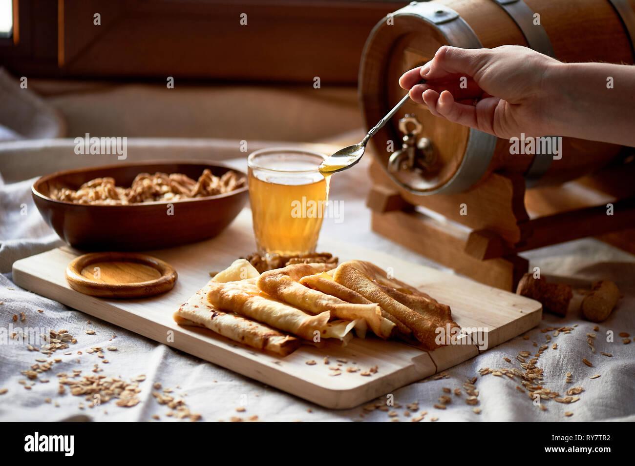 Mead und Pfannkuchen. Russische Gericht für Faschingsdienstag. Abschied vom Winter, die Hand in den Rahmen. Honig vom Löffel tropft auf Pfannkuchen Stockbild