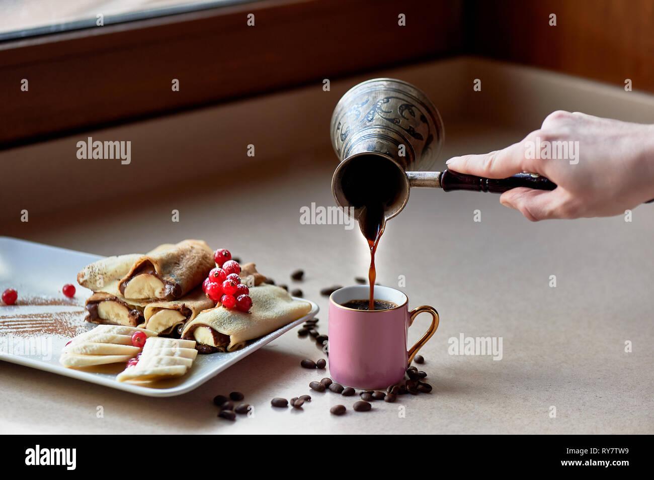 Dessert - heißen Pfannkuchen mit Nutella und Banane. Mit korinthen eingerichtet. Süße Nachspeise. Weiter ist eine Tasse Kaffee. Hand gießt Kaffee von Turki Stockbild