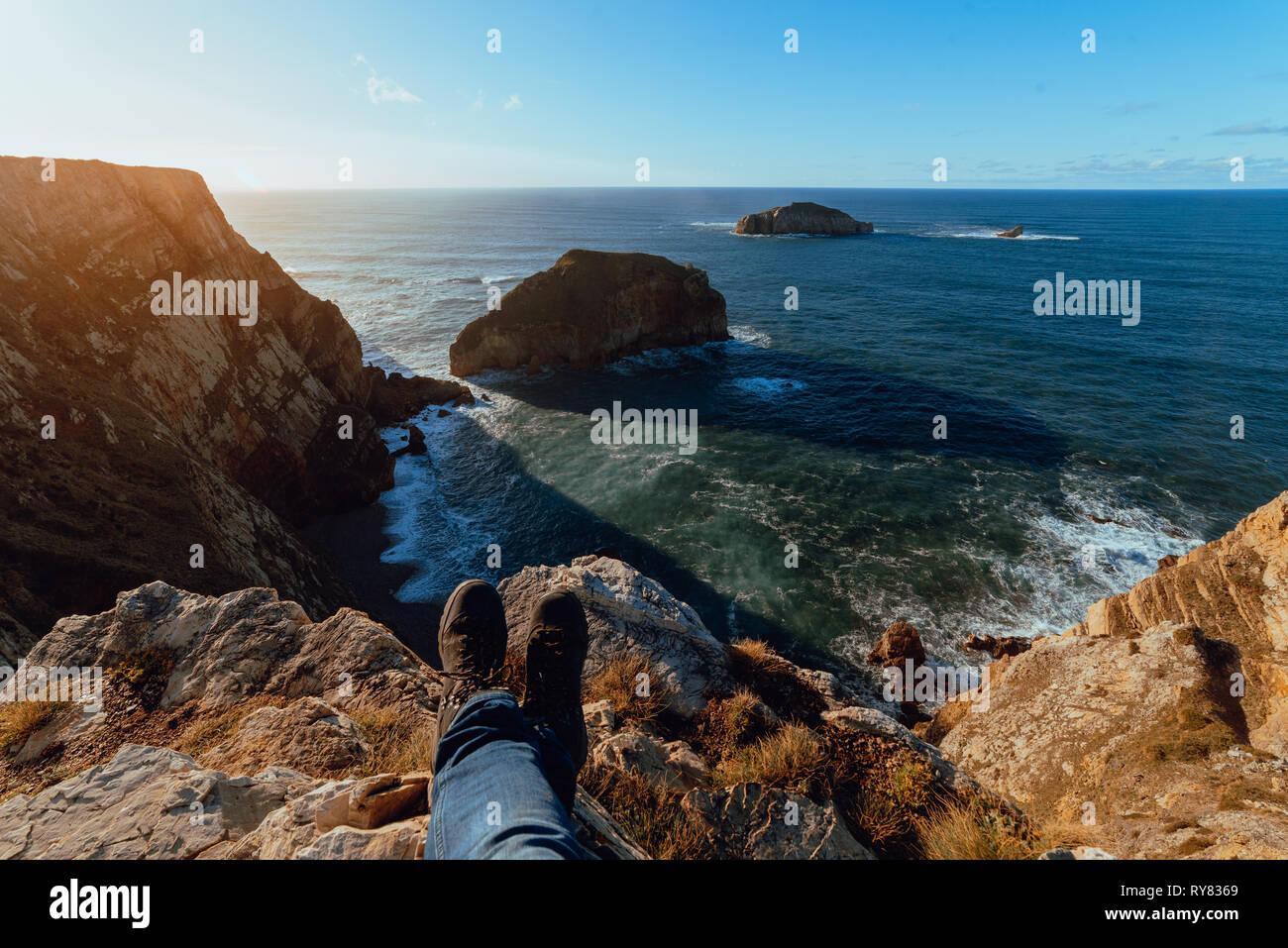 Erntegut Beine der menschlichen saß oben auf der Stone Hill in der Nähe von malerischen Meer in sonniger Tag im Cabo de Penas, Asturien, Spanien Stockbild