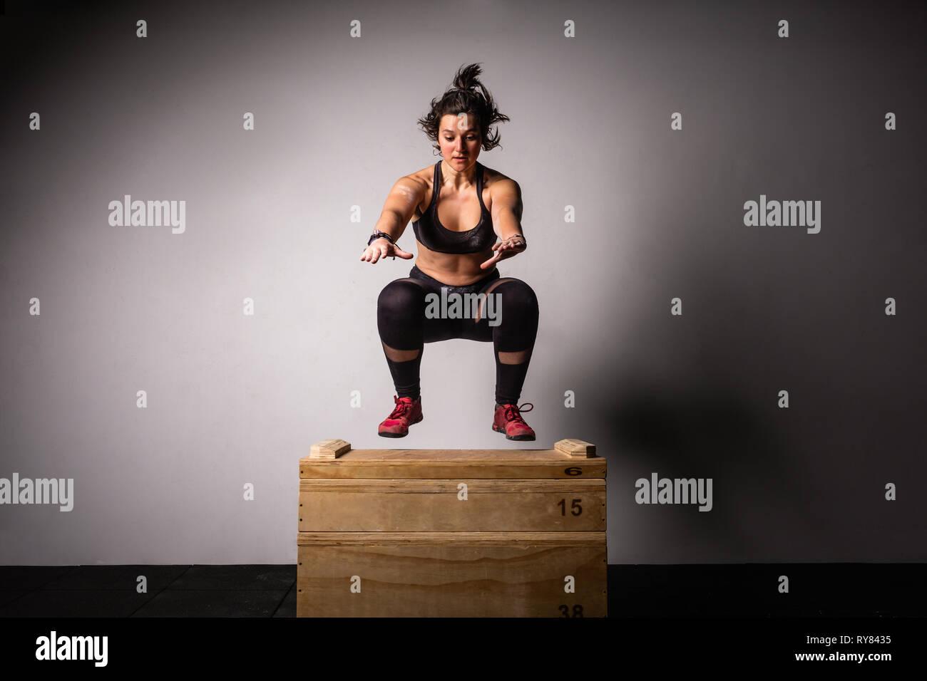 Sportliche junge Dame in Sportswear mit streckte die Hände springen auf Holzkiste im Fitnessraum auf grauem Hintergrund Stockbild