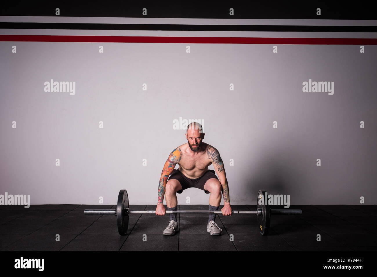 Athletischen jungen konzentriert Kerl in Sportswear upping Barbell in der Turnhalle Stockbild