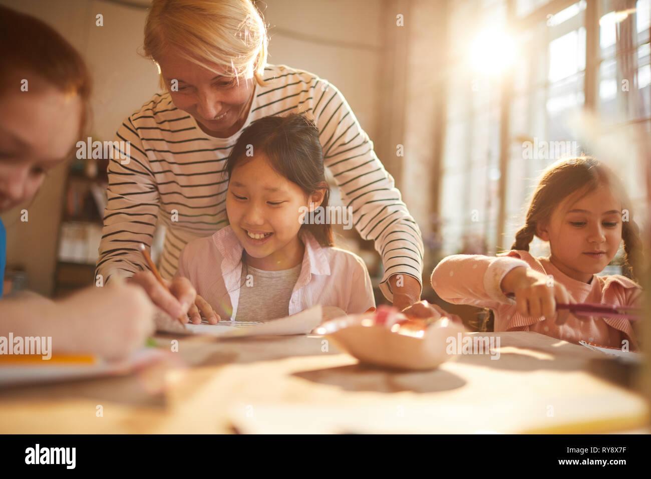 Portrait von einer Frau, die mit einer Gruppe von kleinen Mädchen Malerei im Kunstunterricht, Szene beleuchtet durch heitere Sonnenlicht, Kopie Raum Stockbild