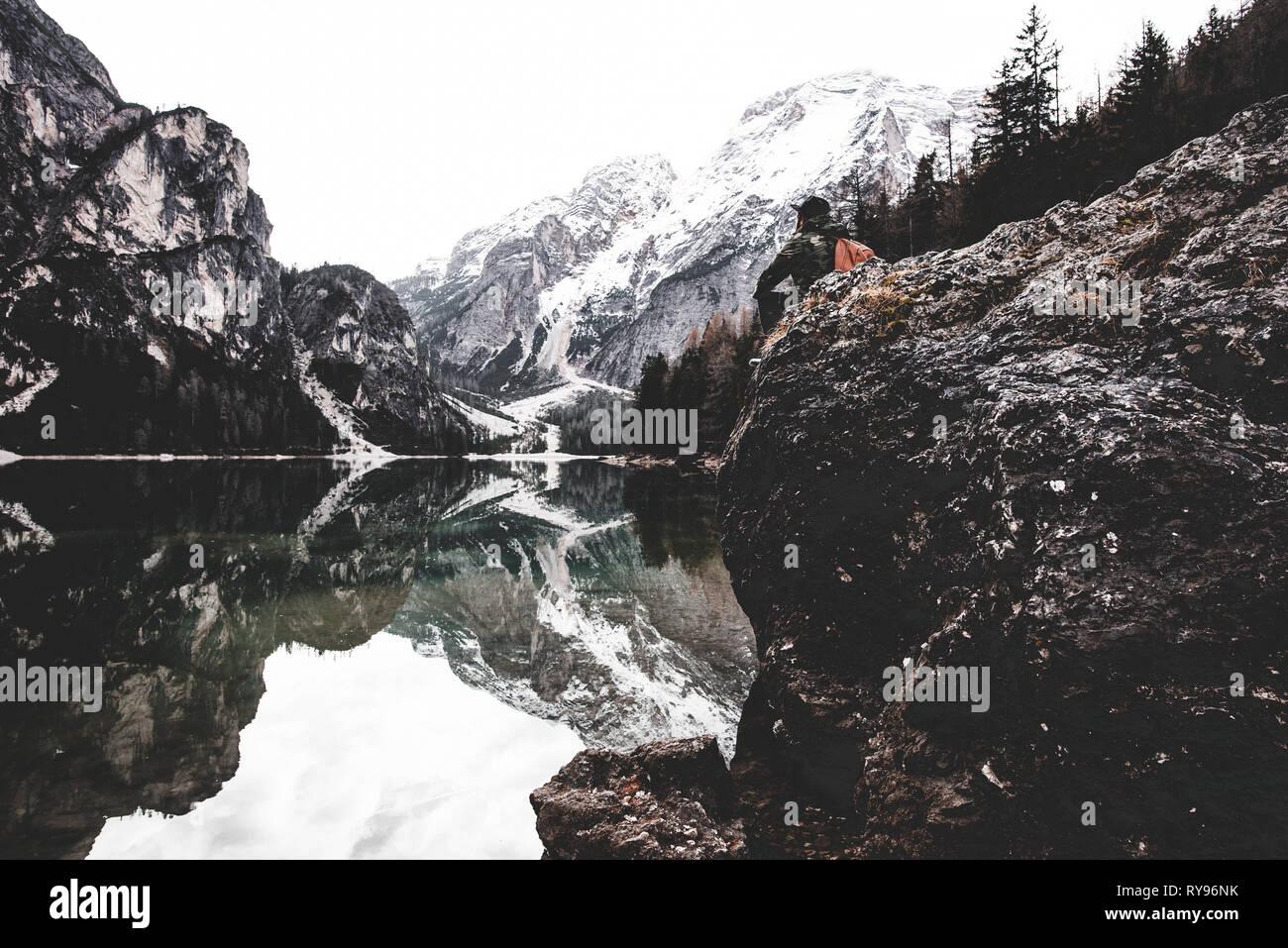 Seitenansicht der männlichen sitzt auf Felsen in der Nähe von fantastischen See und die hohen Berge in Italien Stockbild