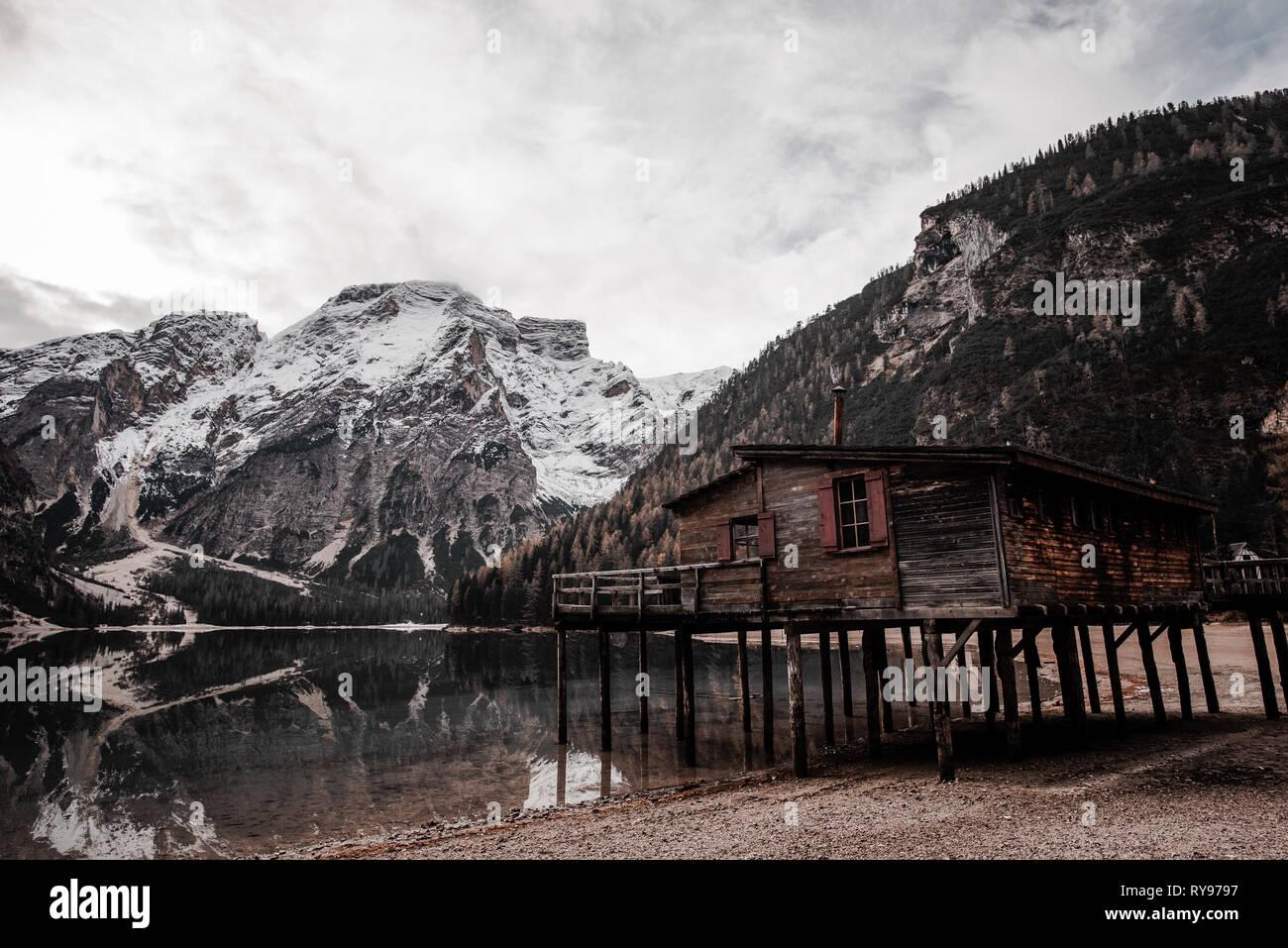 Holzhaus auf Stelzen an der Küste in der Nähe von fantastischen See und Stein hohe Berge und bewölkter Himmel in Italien Stockbild