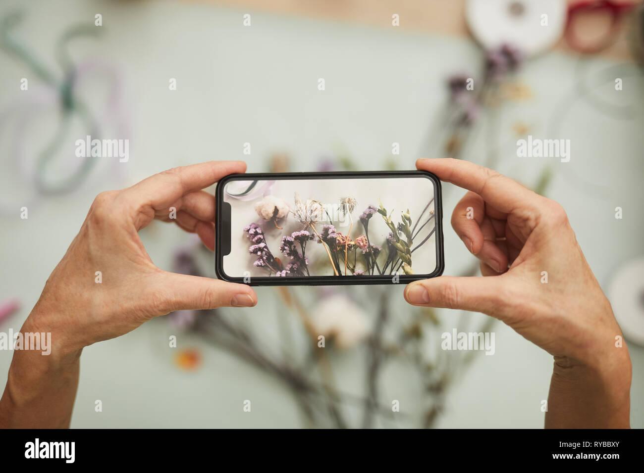 Oben Ansicht Nahaufnahme des unkenntlich Frau unter Mobile Photo von Blume Zusammensetzung in art studio, Kopie Raum Stockbild