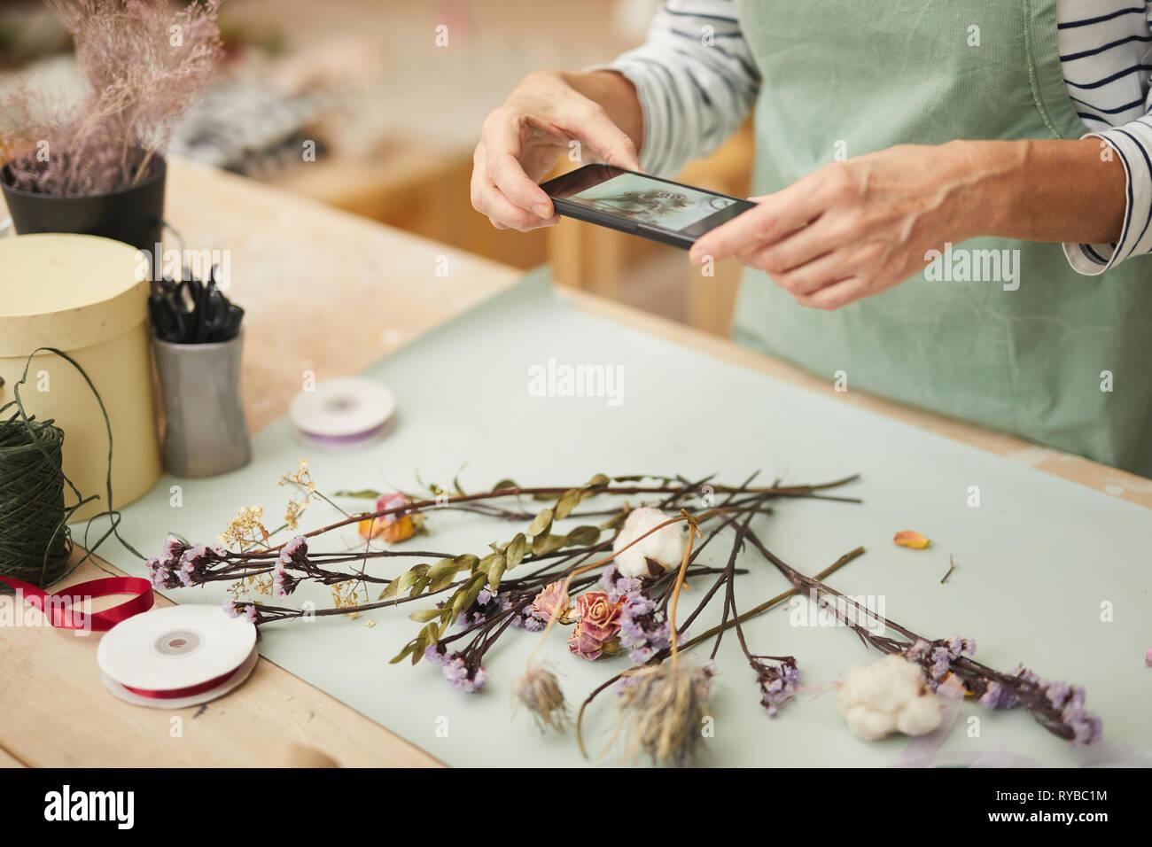 Nahaufnahme des unkenntlich Frau unter Mobile Photo von Blume Zusammensetzung in art studio, Kopie Raum Stockbild