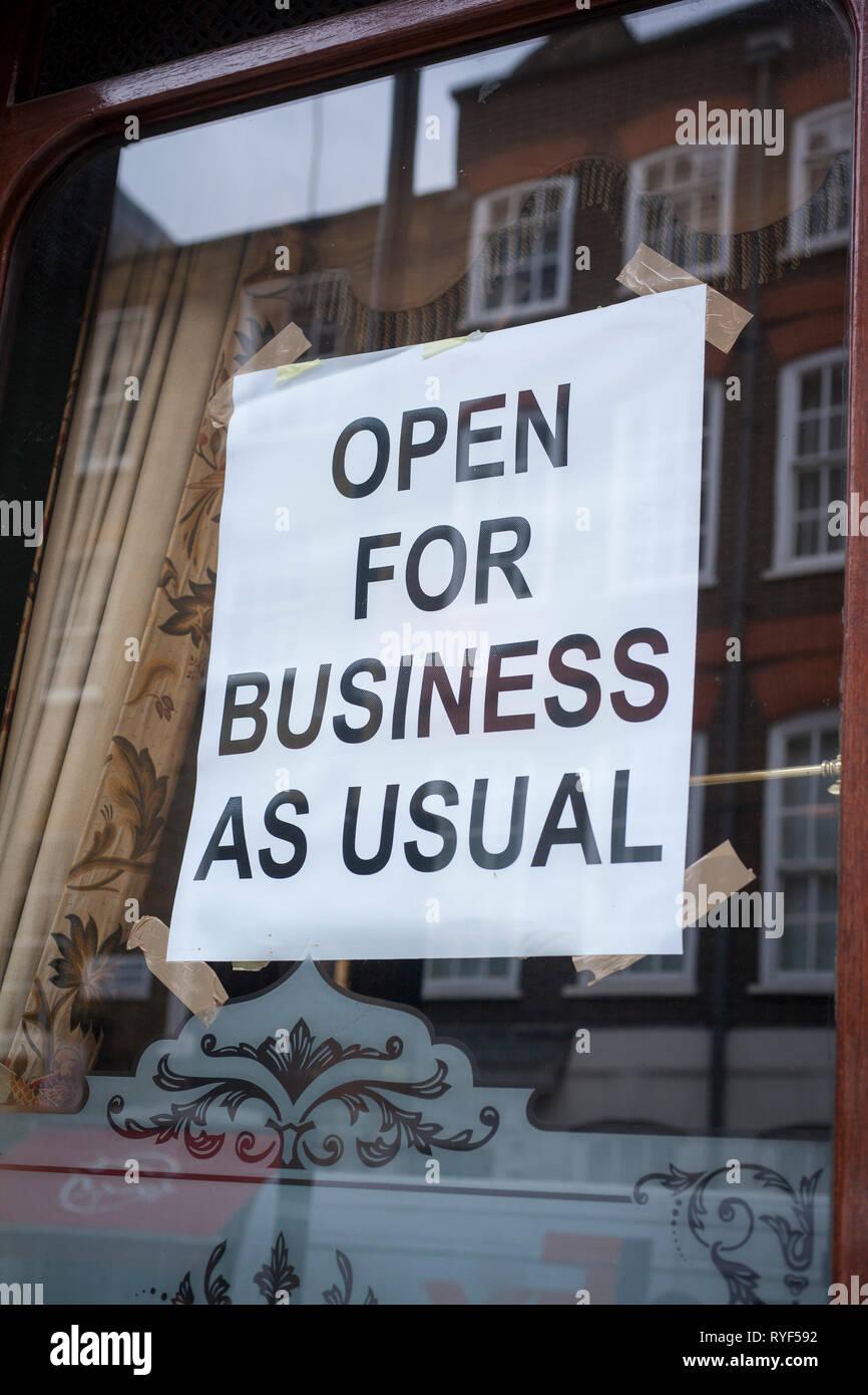 """Open For Business as usual""-Plakat in einem Fenster. Stockfoto"