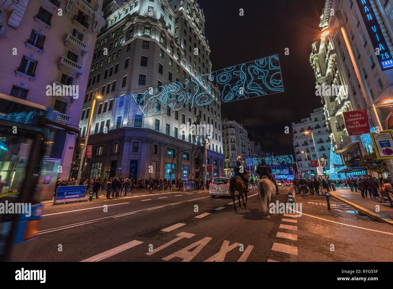 Madrid, Spanien - 26. Dezember 2017: Leute, überfahrt Gran Via Street, geniessen Weihnachtsbeleuchtung Dekoration und Shopping während der Weihnachtszeit. Madrid Stockbild