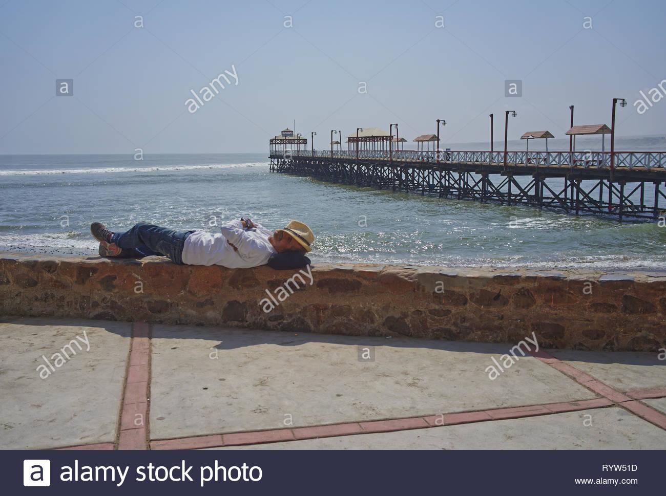 Menschen schlafen auf der Promenade mit der schönen Pir im Hintergrund am Strand von Huanchaco Trujillo Peru Stockfoto