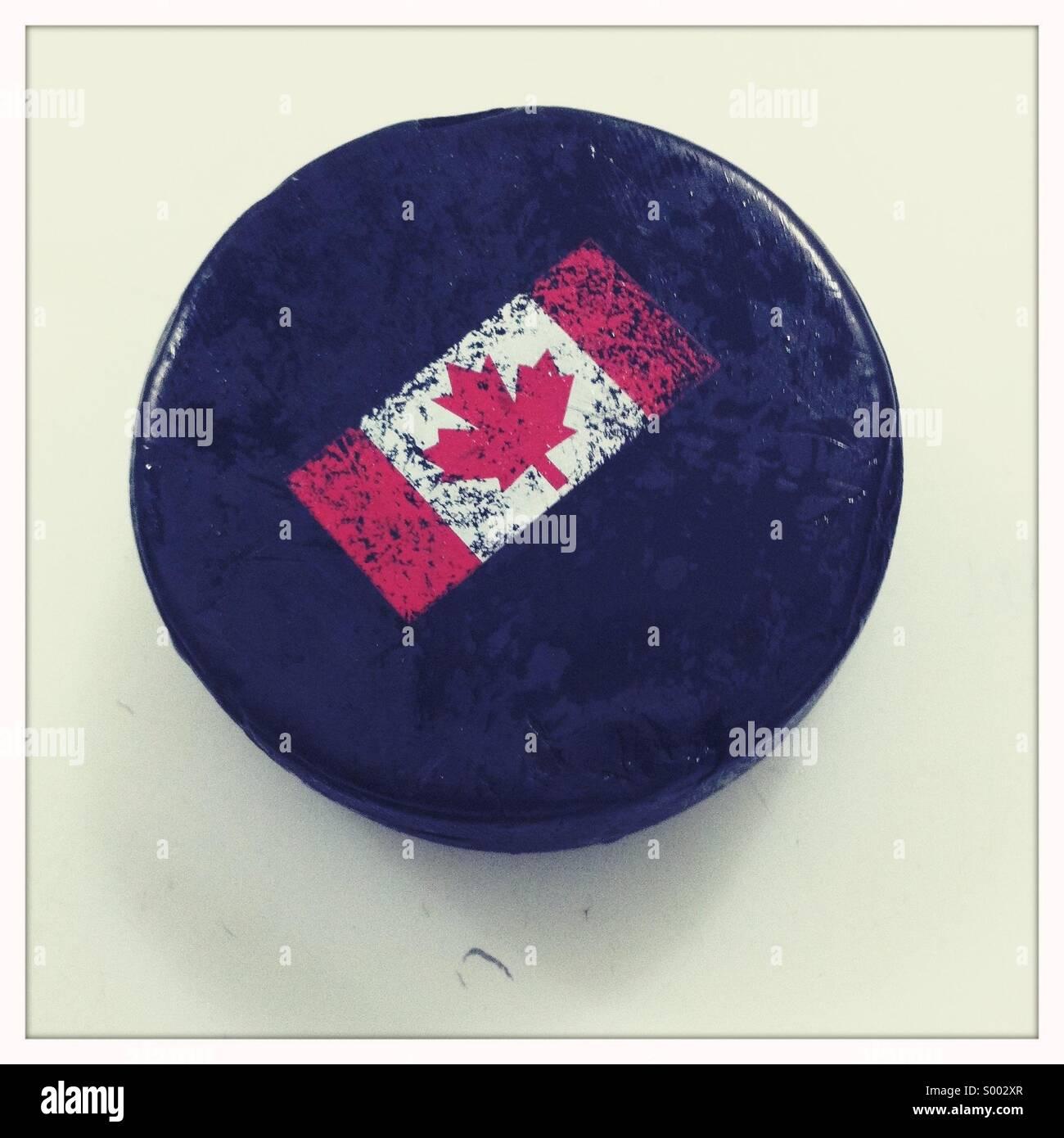 Ein schwarzes Eis-Hockey-Puck mit einer kanadischen Flagge gemalt. Stockbild