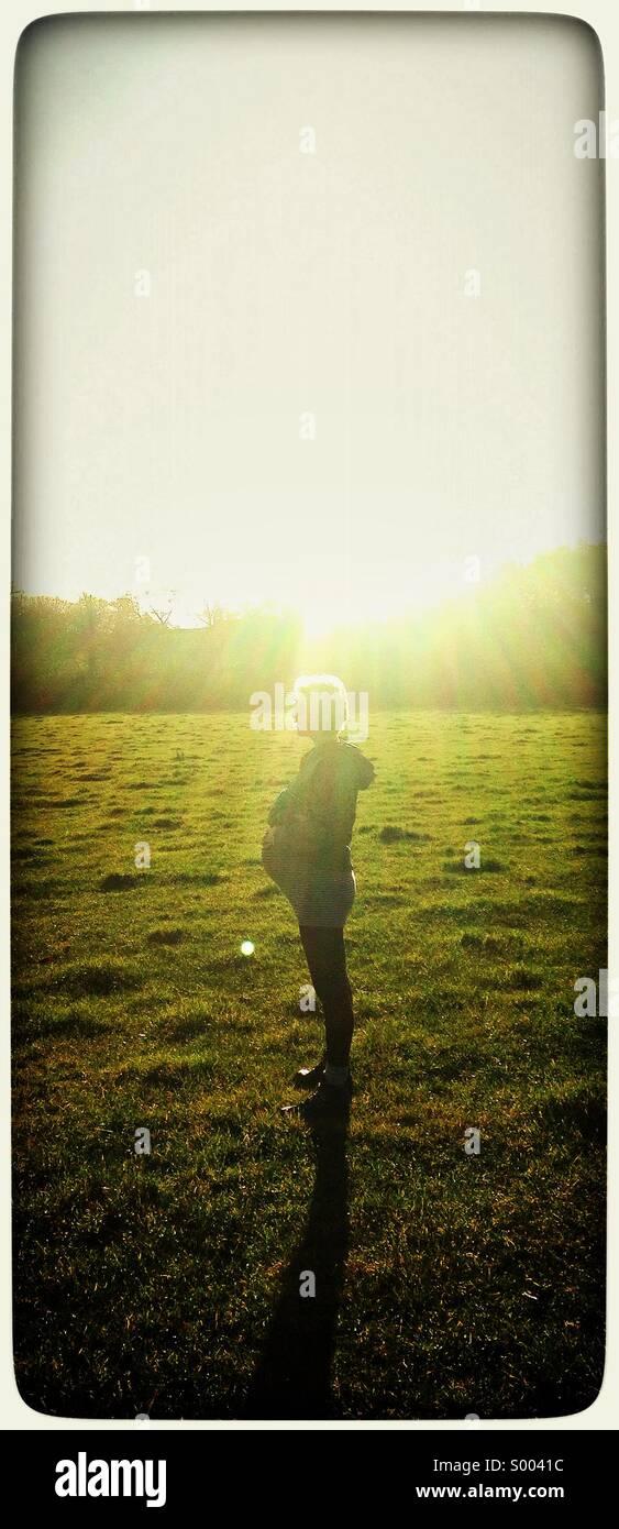 Schwangere Frau, die Hintergrundbeleuchtung durch tief stehender Sonne Stockbild
