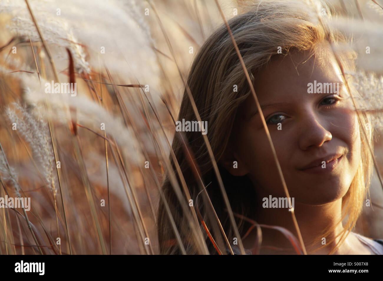 Eine junge Frau geht durch Herbst Gräser. Stockbild