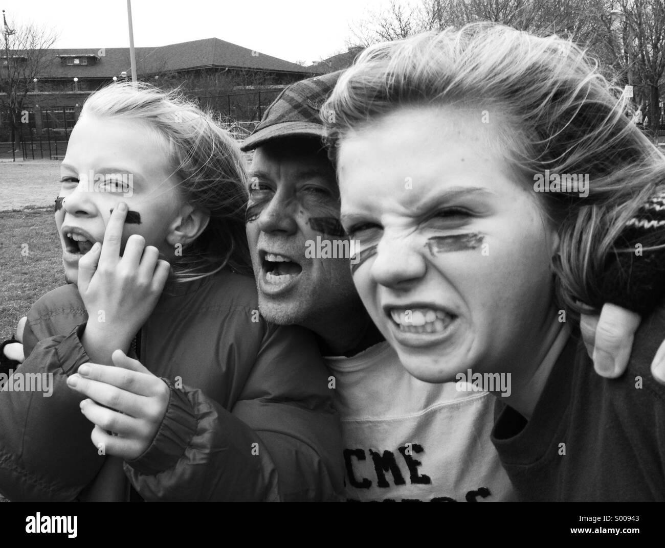 Mach dich bereit für ein Familienspiel des Fußballs, ein Vater und seine Töchter. Stockbild