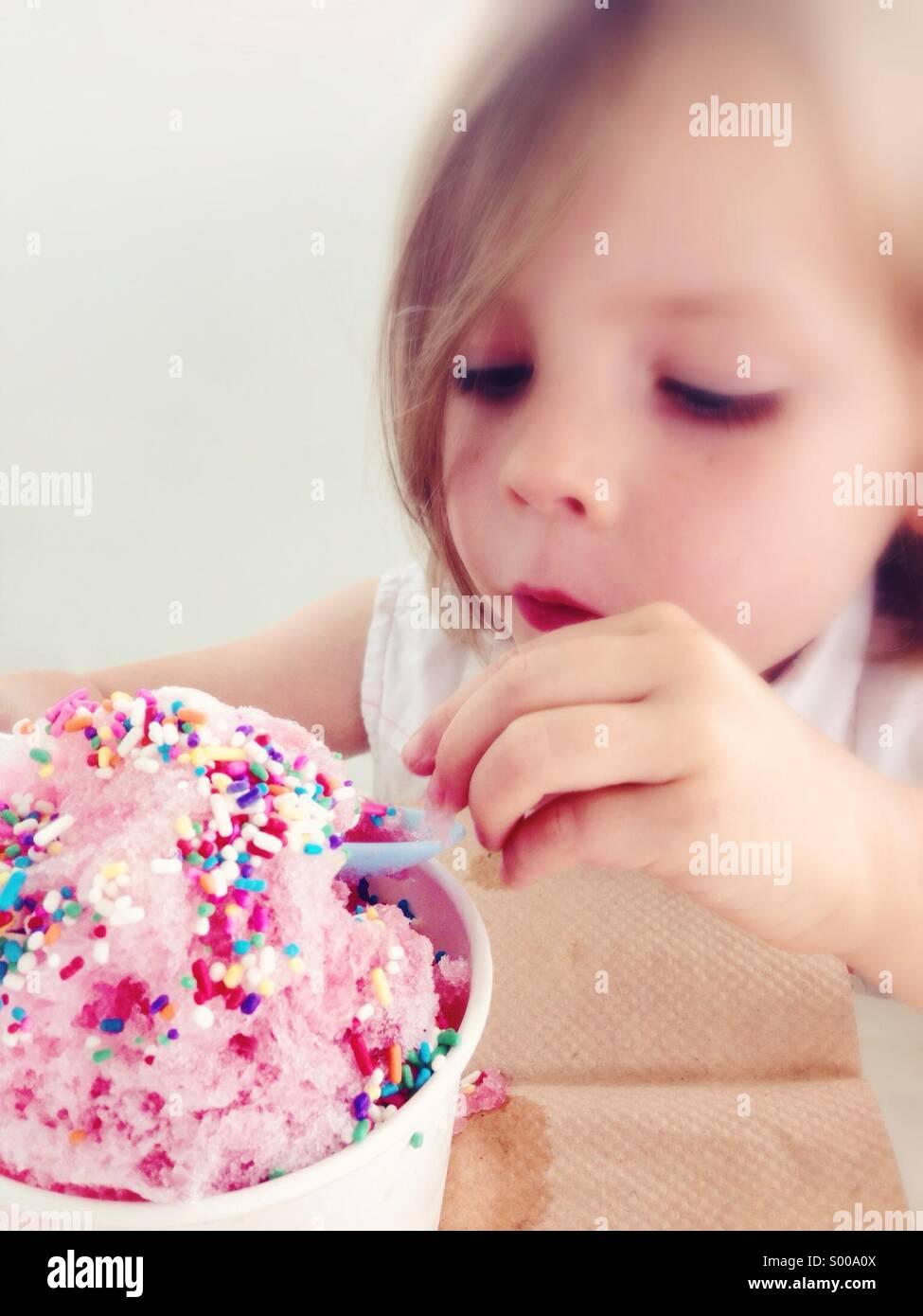 Ein kleines Mädchen genießt eine gefrorene Behandlung mit Streuseln obendrauf Stockbild